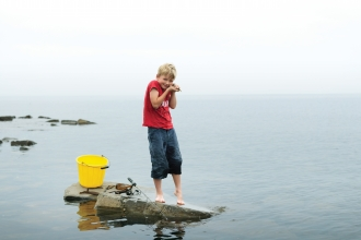 Archie stands on a rock in the sea with a bucket