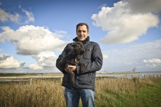 David holding his dog at a wetland