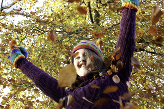 Person throwing autumn leaves in the air
