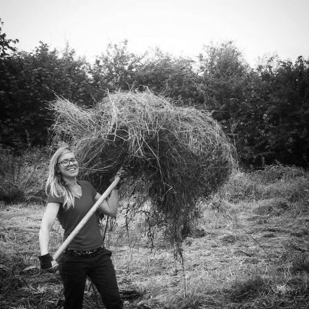 Volunteer Chloe lifts hay