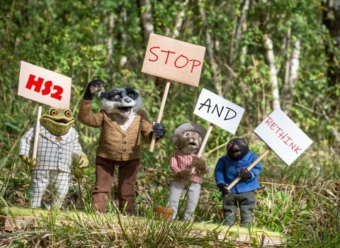 The Wind in the Willows characters carrying campaign placards reading HS2 Stop and Rethink
